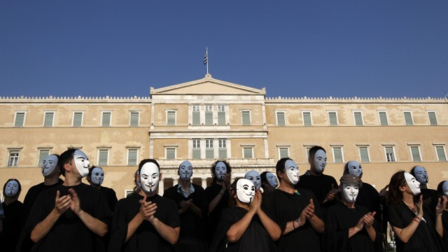 Demonstrators wearing masks protest against the austerity economic measures and corruption in front of the parliament in Athens