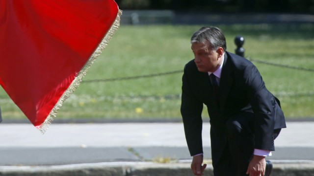 Hungarian Prime Minister Viktor Orban ties his shoelace before a welcome ceremony for Chinese Premier Wen Jiabao in front of the Parliament building in Budapest