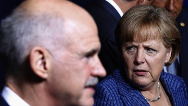 Greece's Prime Minister Papandreou walks past Germany's Chancellor Merkel after a family photo at an European Union leaders summit in Brussels