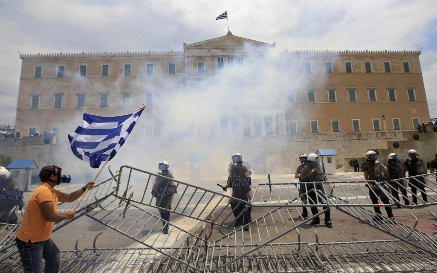 An anti-austerity protester confronts riot police in front of the parliament in Athens