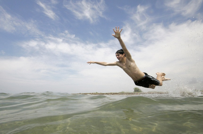A boy jumps into the waters of the Black Sea in the village of Molochnoye outside the town of Yevpatoria