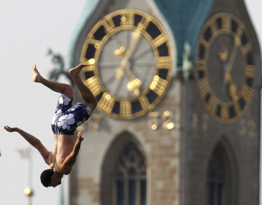 A young man jumps from a 10 metre-high platform into Lake Zurich during hot summer weather in Zurich