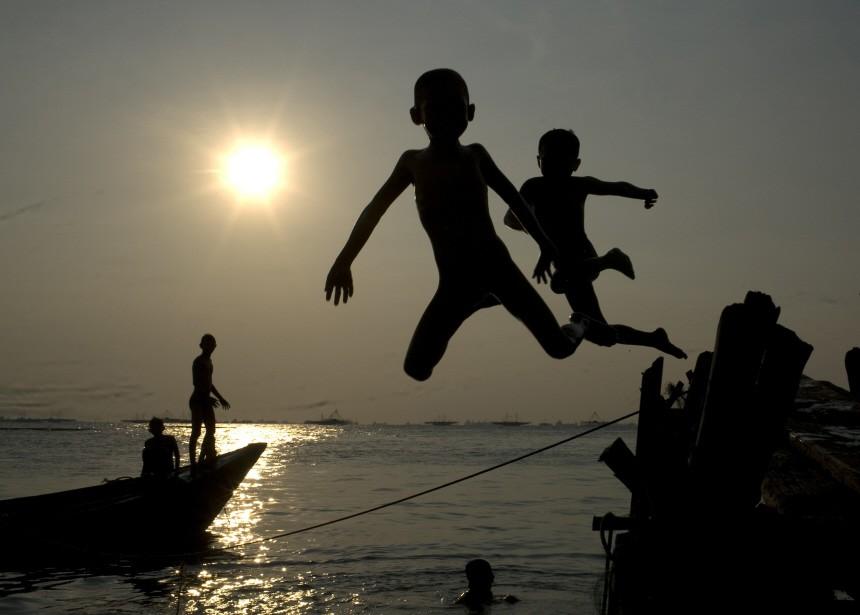 Children jump into the sea at Marunda beach in Jakarta
