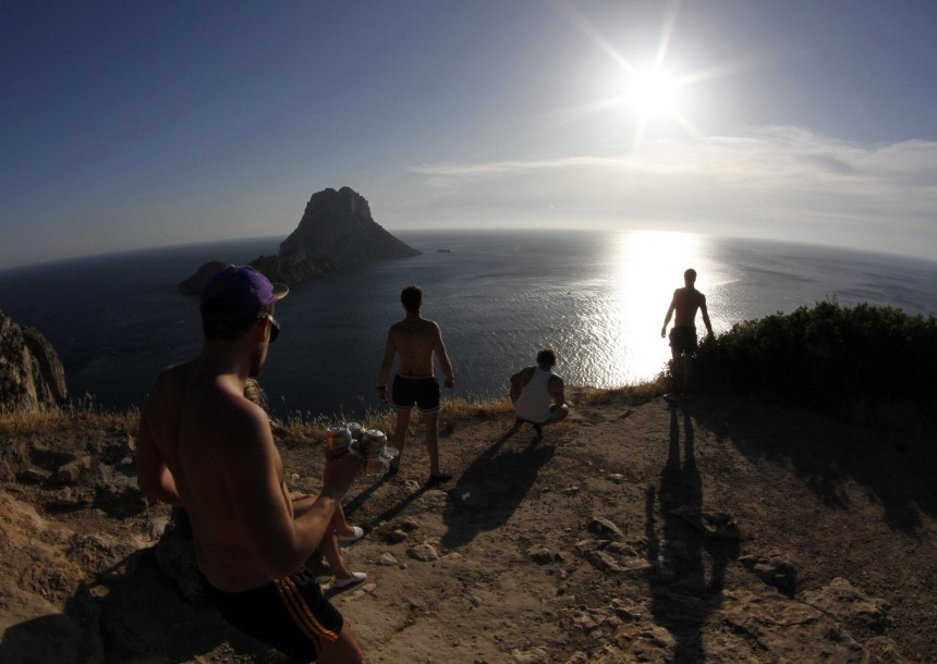 Tourists meet to watch the sunset at Es Vedra cliffs, on the Spanish Balearic island of Ibiza