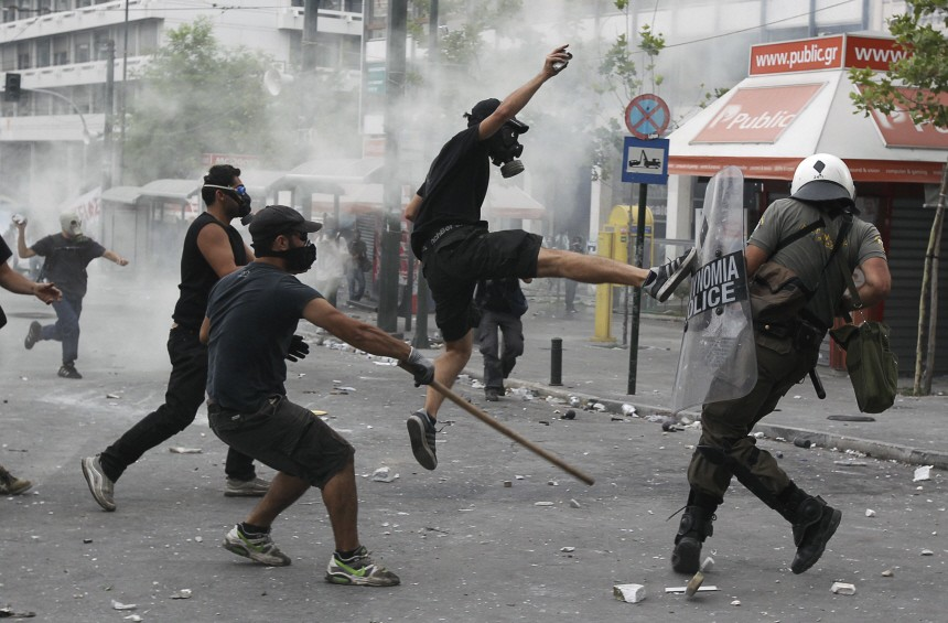 Protesters attack a policeman during violent protests around Syntagma square in Athens