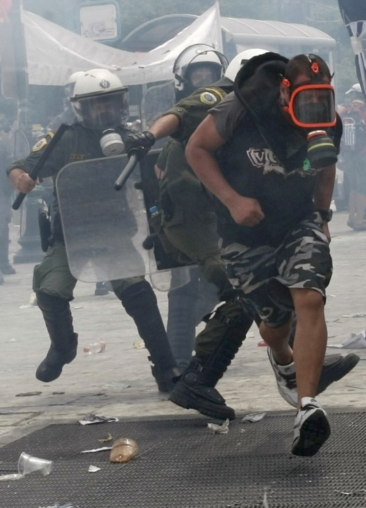 A demonstrators is chased by riot police during anti-austerity protests in Athens