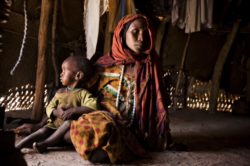 A displaced ethnic Arab woman spends the heat of the day in a grass hut in eastern Chad