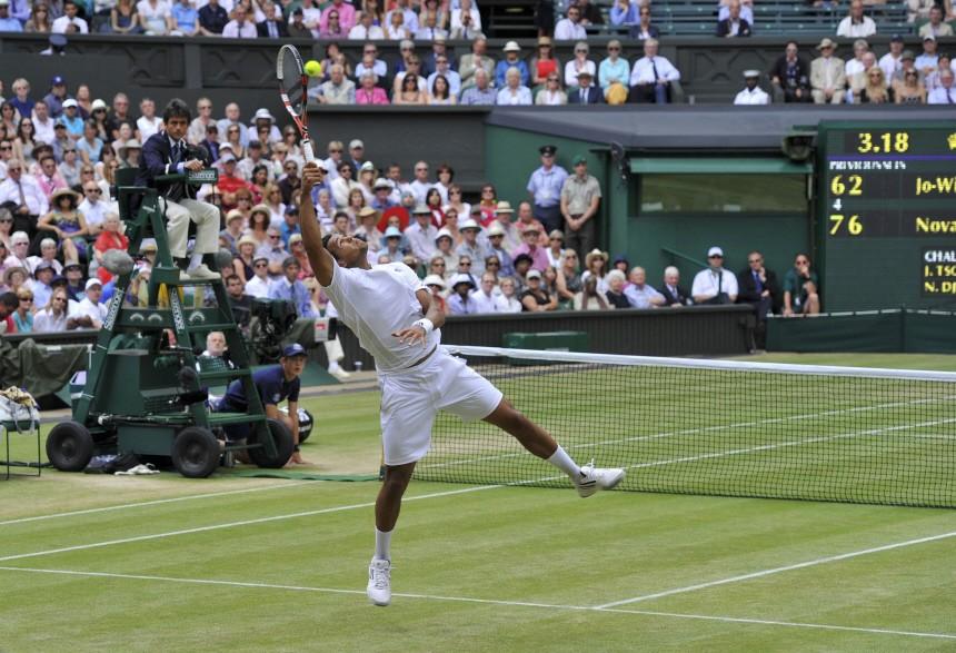 Jo-Wilfried Tsonga of France hits a return to Novak Djokovic of Serbia during their semi-final match at the Wimbledon tennis championships in London