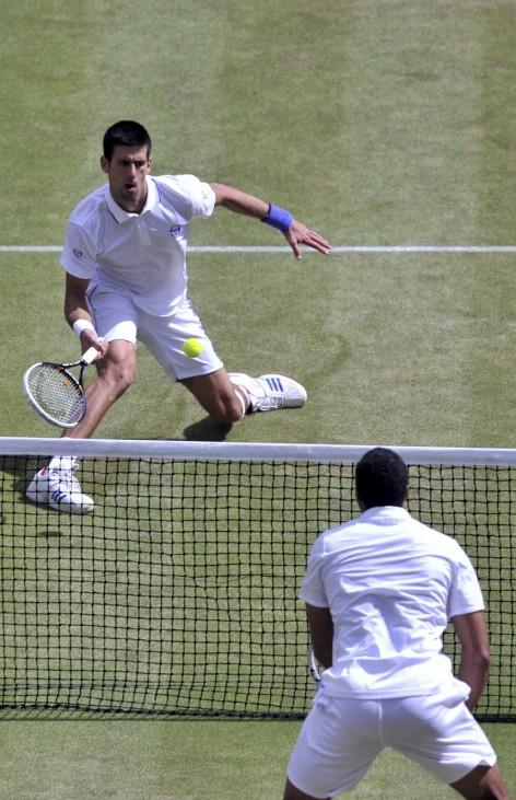 Novak Djokovic of Serbia hits a return to Jo-Wilfried Tsonga of France during their semi-final match at the Wimbledon tennis championships in London