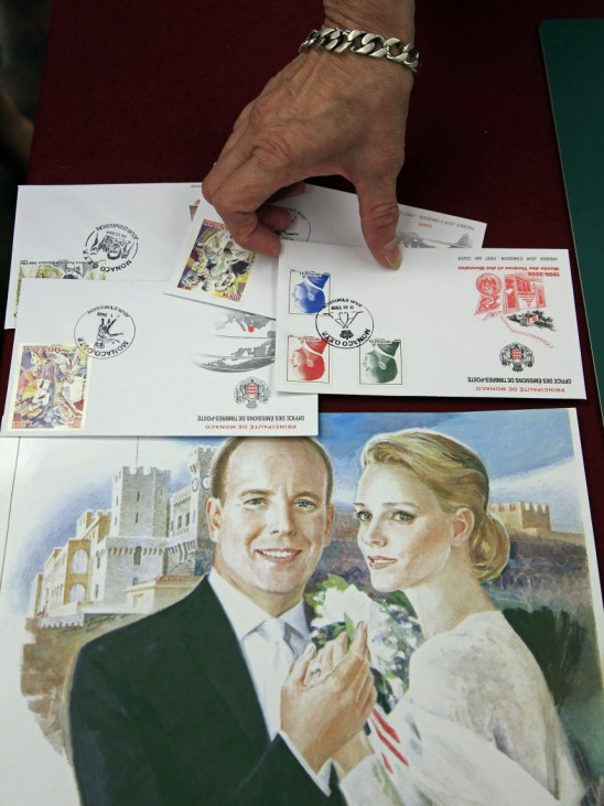 An official displays commemorative stamps to mark the wedding of Prince Albert II of Monaco and his fiancee Charlene Wittstock in Monaco