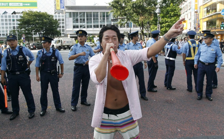 A Japanese soccer fan plays with a vuvuzela as he celebrates Japan's victory over the U.S. in their Women's World Cup final soccer match in Frankfurt, on the street in Tokyo