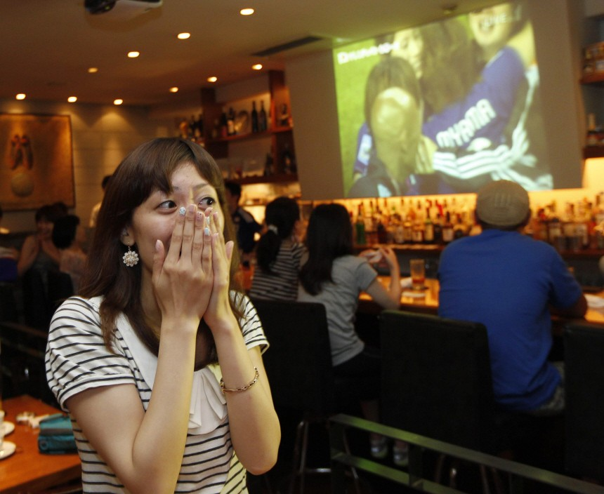 A woman reacts after Japan beat the U.S. during the Women's World Cup final soccer match in Frankfurt, as she watches a TV broadcast at a bar in Tokyo