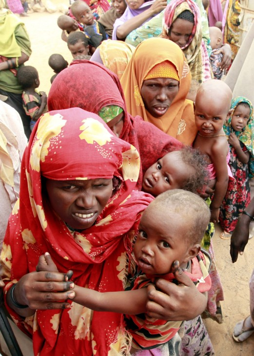 Internally displaced women carry their malnourished children as they queue at a mobile medical facility at the Hiran IDP settlement in Galkayo