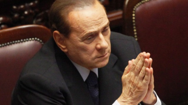 Italian Premier Silvio Berlusconi reacts at the lower house of pa