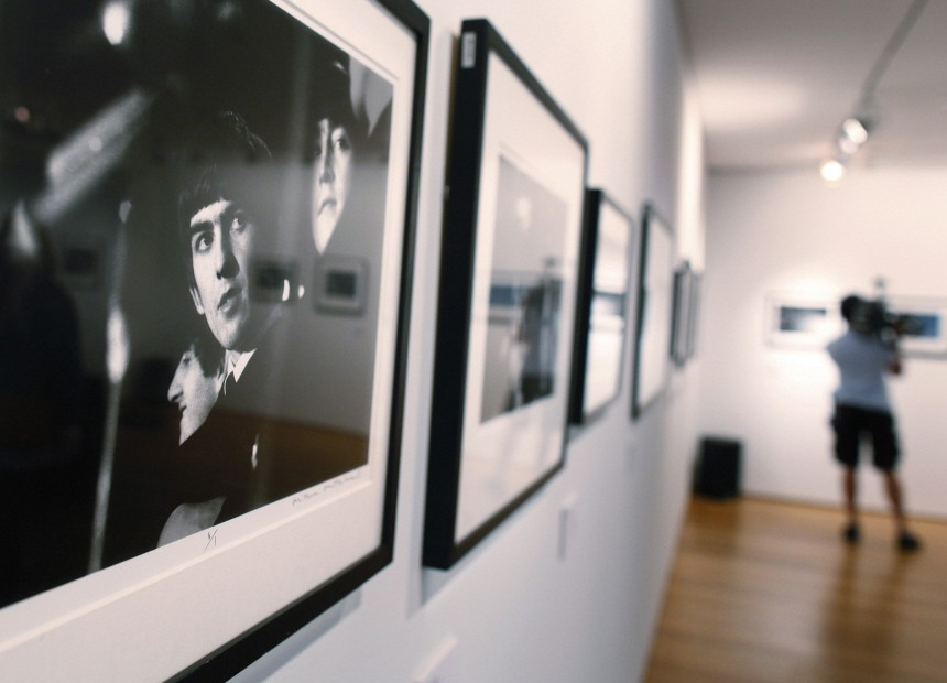 A cameraman films photographs from 'The Beatles Illuminated: The Discovered Works of Mike Mitchell', on display during a press preview at Christie's auction house in New York