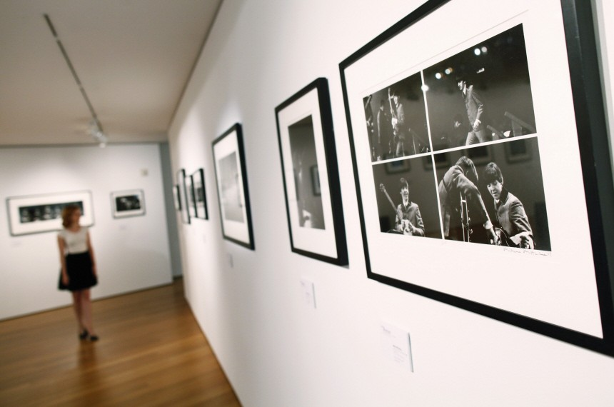 A visitor looks at photographs from 'The Beatles Illuminated: The Discovered Works of Mike Mitchell', on display during a press preview at Christie's auction house in New York