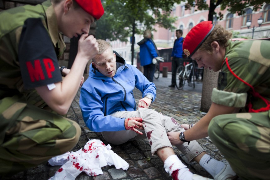 Military personnel help an injured man at the site of a powerful explosion that rocked central Oslo