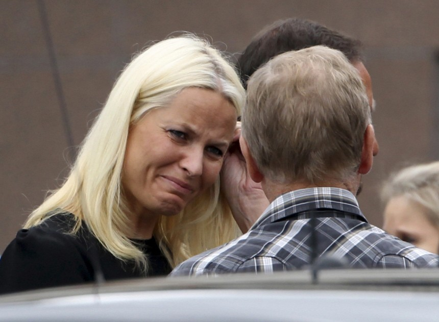 Norway's Crown Princess Mette Marit reacts as she talks with relatives of the victims of a rampage on nearby Utoeya island after a memorial service at a church in Sundvollen