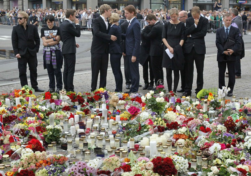 Survivors and relatives of a shooting rampage on the Utoeya island mourn in front of a sea of flowers and candles following a memorial service in Oslo cathedral