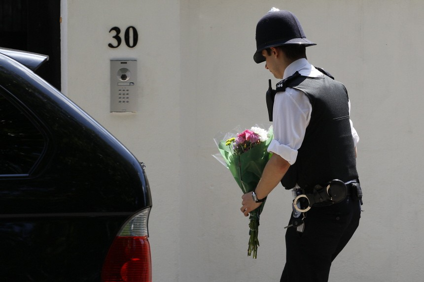 A police officer places flowers outside the home of Amy Winehouse in London
