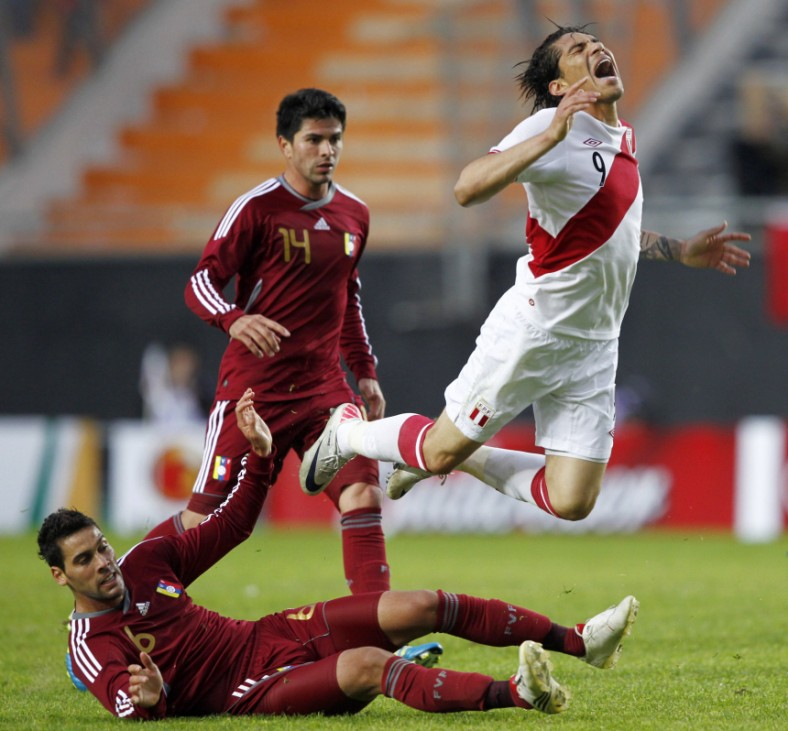 Peru's Paolo Guerrero falls after being fouled by Venezuela's Gabriel Cichero as teammate Franklin Lucena runs behind during their soccer match to decide third and fourth place at the Copa America in La Plata