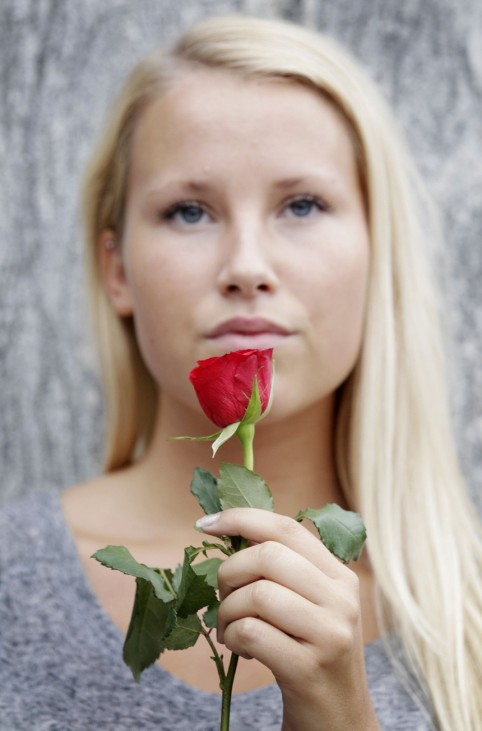 A woman holds a flower during a memorial march in Oslo