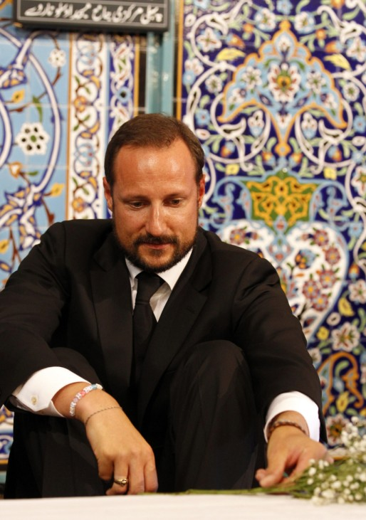 Norway's Crown Prince Haakon arranges flowers inside the World Islamic Mission Mosque in Oslo