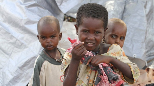 Internally displaced Somali children stand outside their shelter at a camp in capital Mogadishu