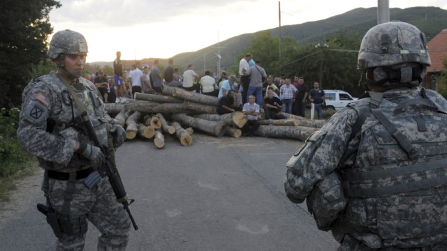 U.S. NATO soldiers look at Kosovo Serbs sitting on the road blockade in the village of Zupce