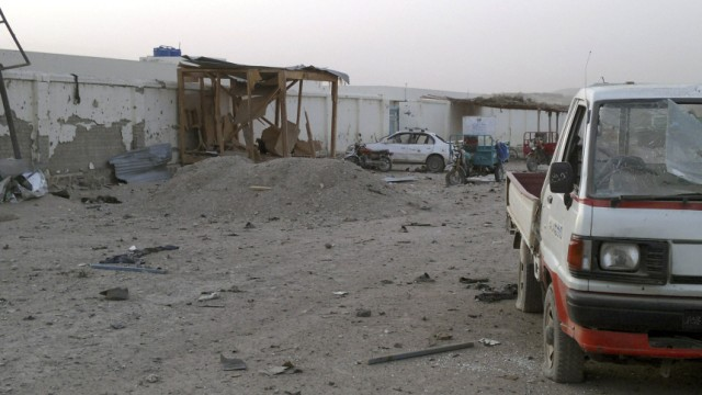 Damaged vehicles are seen inside the government compound in Uruzgan province