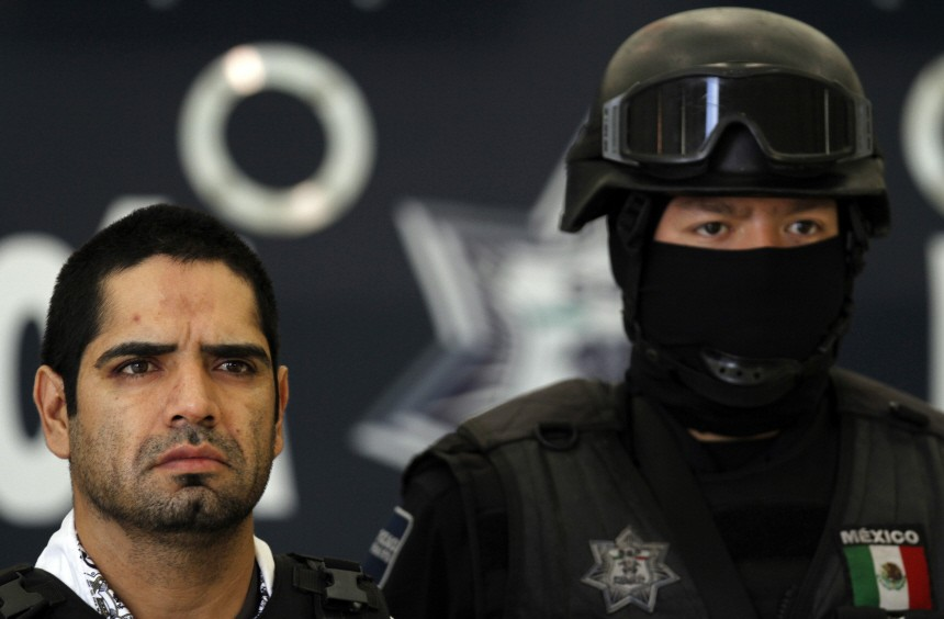 Federal police escort 'El Diego' as he is presented to the media during a news conference at the federal police headquarters in Mexico City