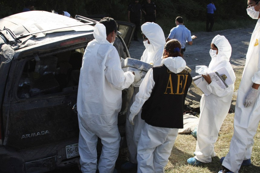 Members of a forensic team unload drug packages from the wreckage of a SUV after a shootout in the municipality of Sabinas Hidalgo