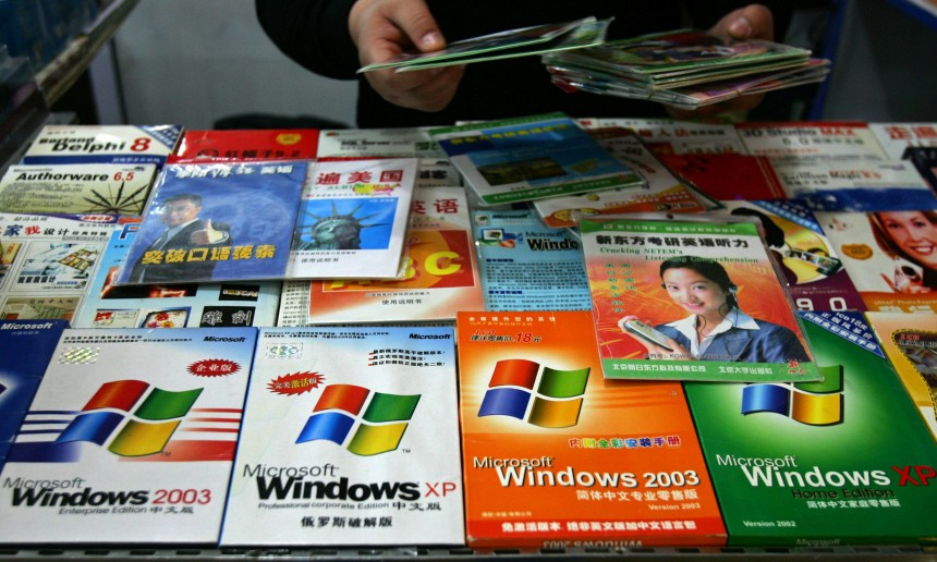 File photo of a vendor arranging pirated Microsoft software at a store in Beijing