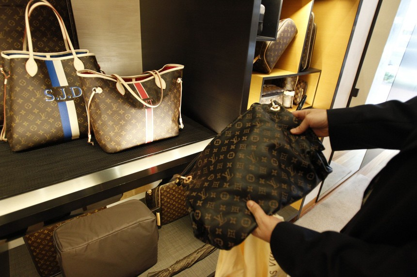 File photo shows a fake LVMH handbag purchased and shipped from a China-based online website next to products on display at a Louis Vuitton store in Chevy Chase, Maryland