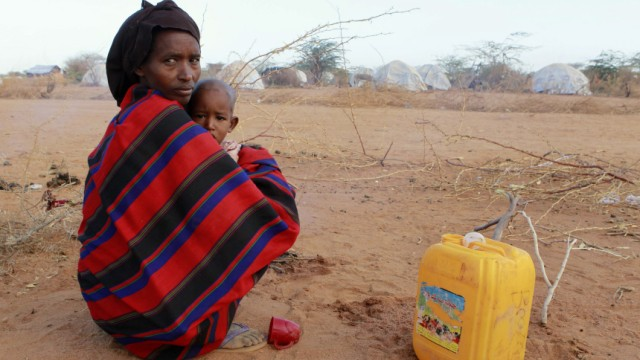 A newly arrived refugee woman and her child from Baidoa in Somalia sit in the open as they camp with their belongings outside Ifo refugee camp in Dadaab