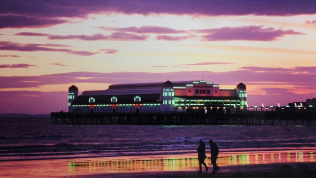 Couple walks past the Grand Pier at dusk at Weston-Super-Mare in southwest England