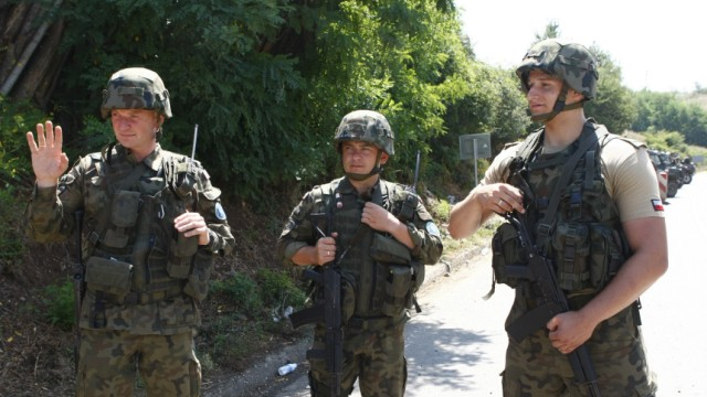 Poland's KFOR soldiers stand on the road in the village of Leposavic near Mitrovica