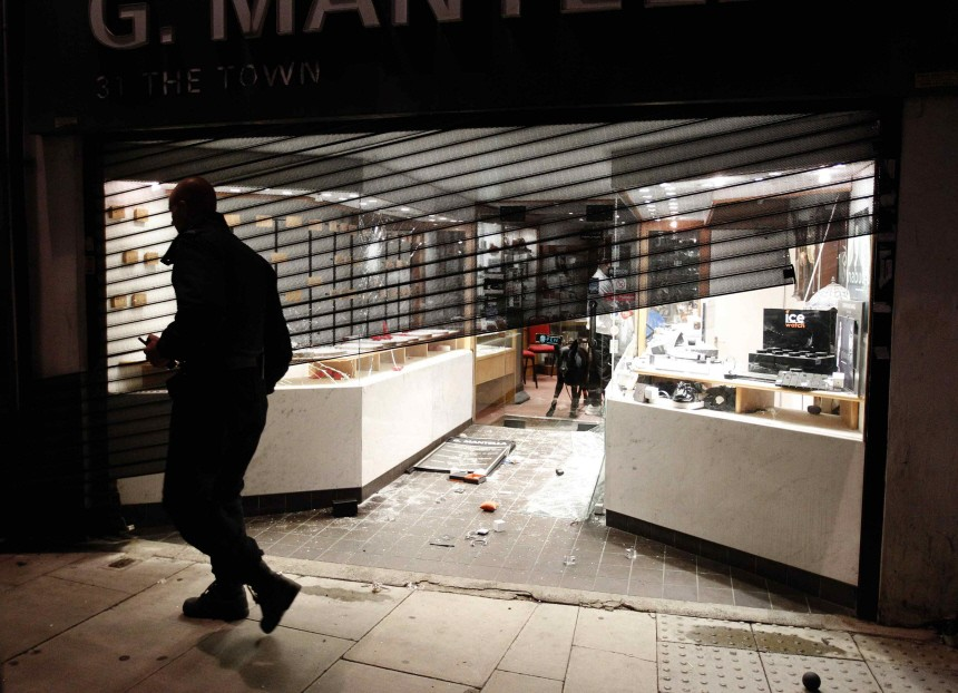 A policeman walks past a damaged jewellery shop in Enfield, north London