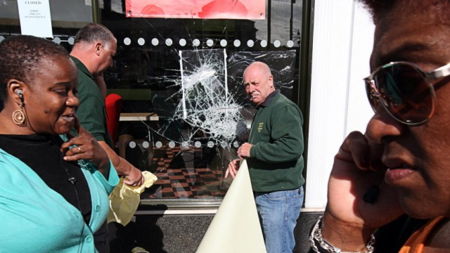 Pedestrians walk past workers fixing a broken glass window at a McDonalds restaurant after overnight looting in Brixton
