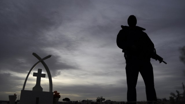 A police officer stands guard during the funeral of victims killed at a family birthday party, in Ciudad Juarez