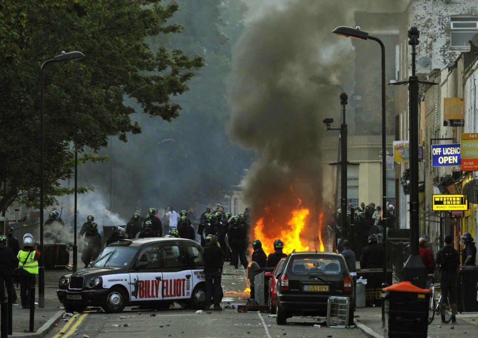 Police officers in riot gear block a road near a burning car on a street in Hackney, east London