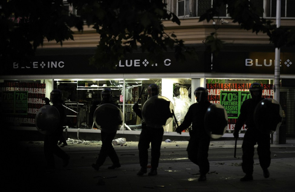 Riot police charge past a looted shop on Peckham High Street in south London