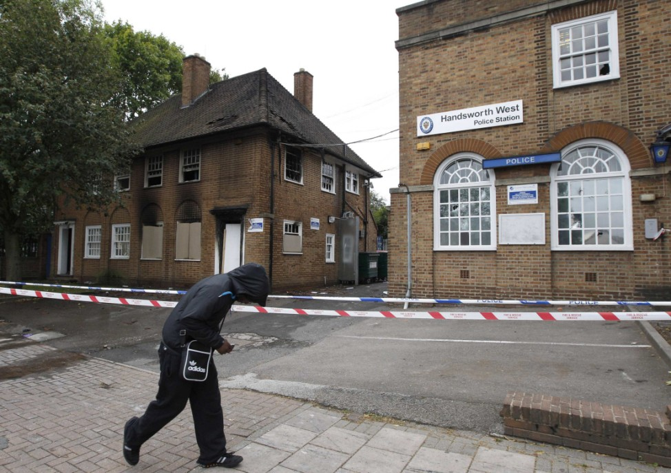 A man walks past Handsworth Police Station, damaged by fire, after disturbances in the Handsworth area of in Birmingham