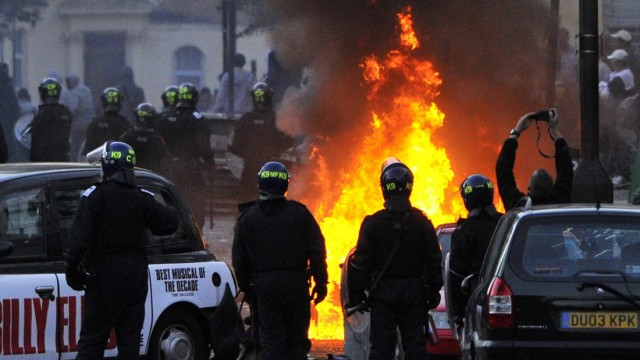 Police officers stand near a barricade of burning and vandalised cars on a street in Hackney