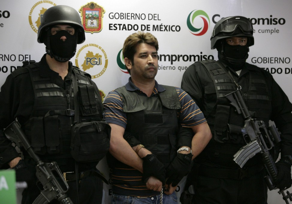 Police officers escort Oscar Garcia Montoya (C), alleged leader of the 'Mano con Ojos' (Hand with Eyes) organization, as he is presented to the media during a news conference in Toluca
