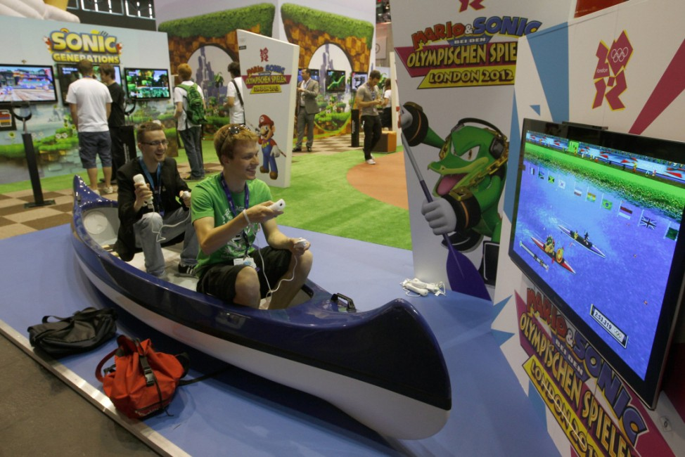 Visitors sit in a canoe and play a game at the Nintendo exhibition stand during the Gamescom 2011 fair in Cologne