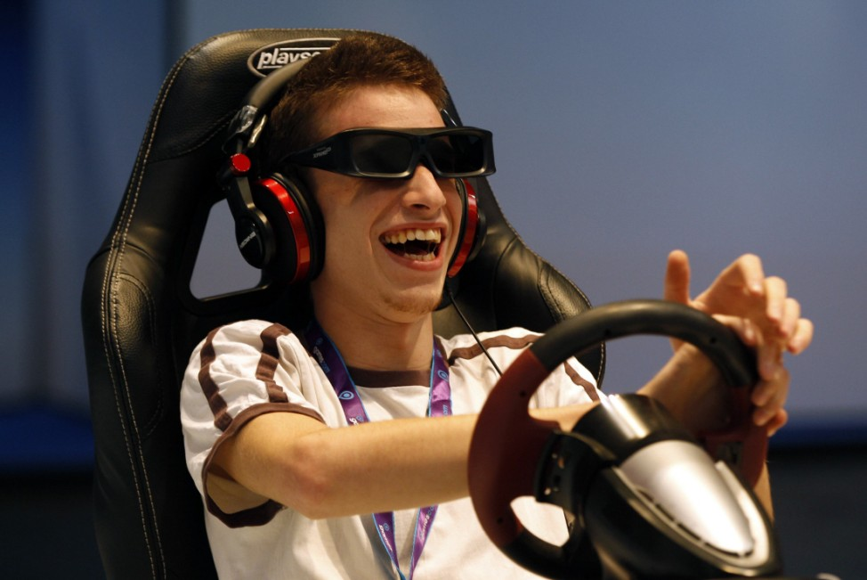 A visitor wearing 3D glasses plays a with Playstation game at an exhibition stand during Gamescom 2011 in Cologne