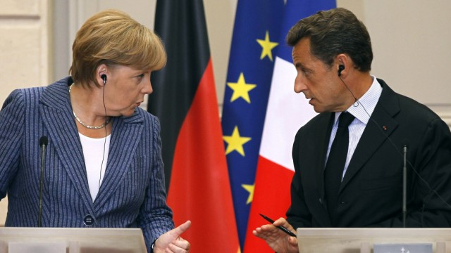 France's President Sarkozy and German Chancellor Merkel talk during a news conference at the Elysee Palace in Paris