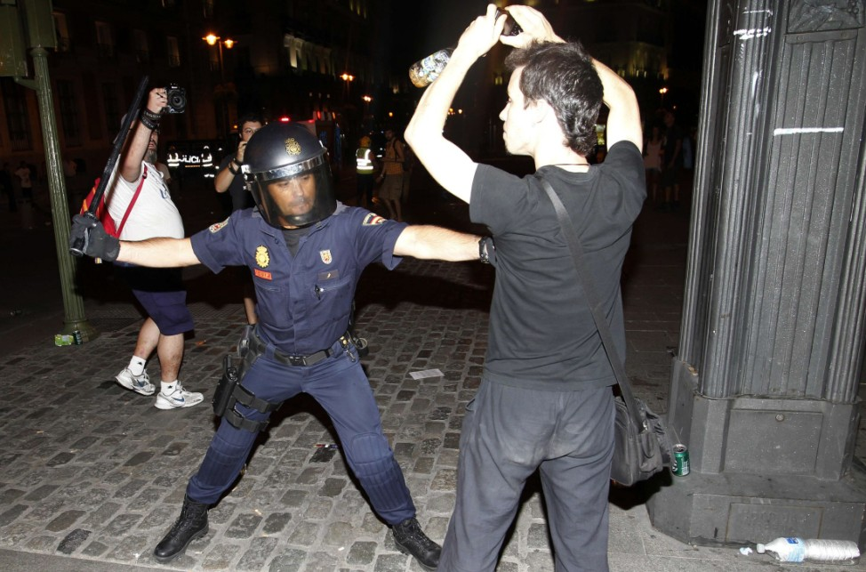 Policemen scuffle with protesters during a demonstration against what they claim is the expensive cost of the papal visit in central Madrid coinciding with the second day of the World Youth Day meeting