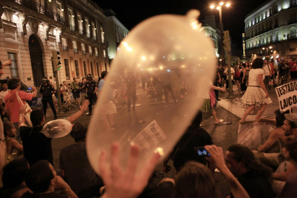 A protester holds a blown-up condom as they perform a sit-in next to police after a demonstration against what they claim is the expensive cost of the papal visit in central Madrid coinciding with the second day of the World Youth Day meeting